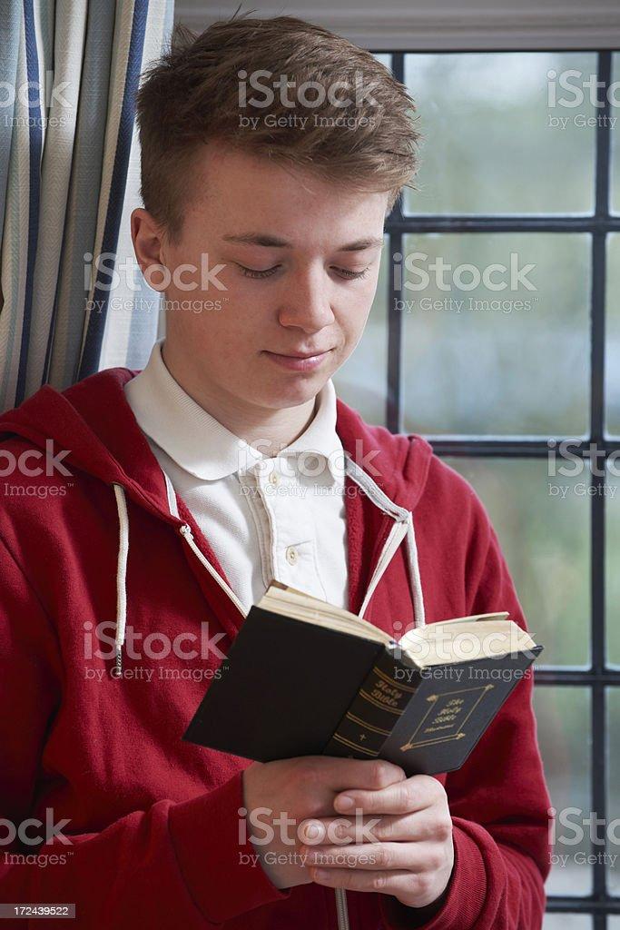 Teenage Boy Reading Bible At Home royalty-free stock photo