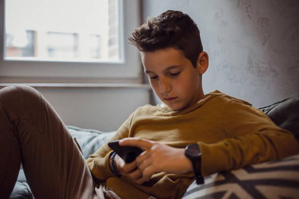teenage boy relaxing in seinem schlafzimmer - jugendalter stock-fotos und bilder