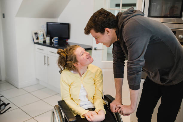 Teenage Boy Relaxing with Disabled Sister at Home Teenage boy is relaxing at home with his disabled sister who is in a wheelchair. als stock pictures, royalty-free photos & images