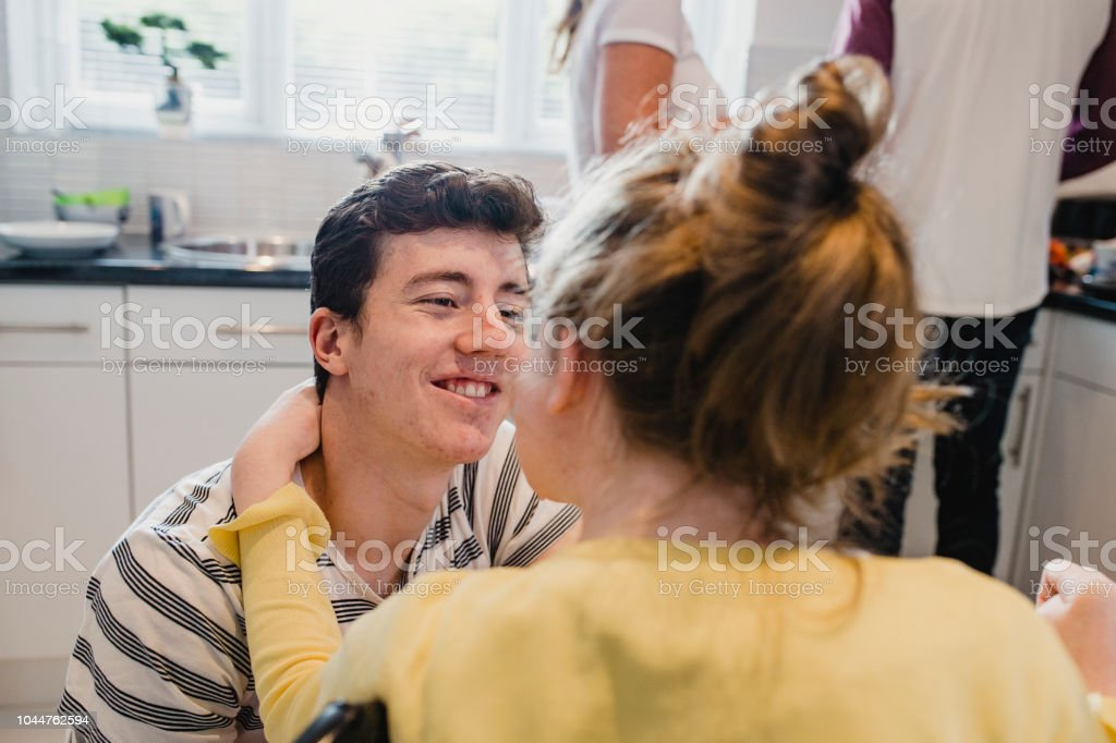 Teenage Boy Relaxing with Disabled Sister at Home stock photo
