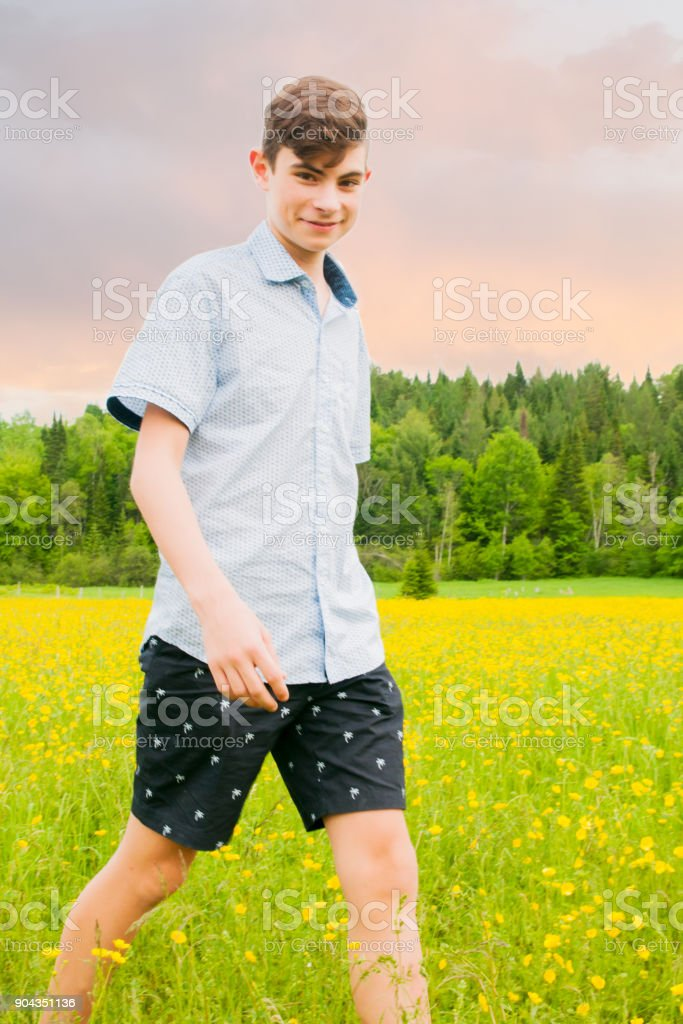Teenage boy running and walking in a yellow field at sunset stock photo