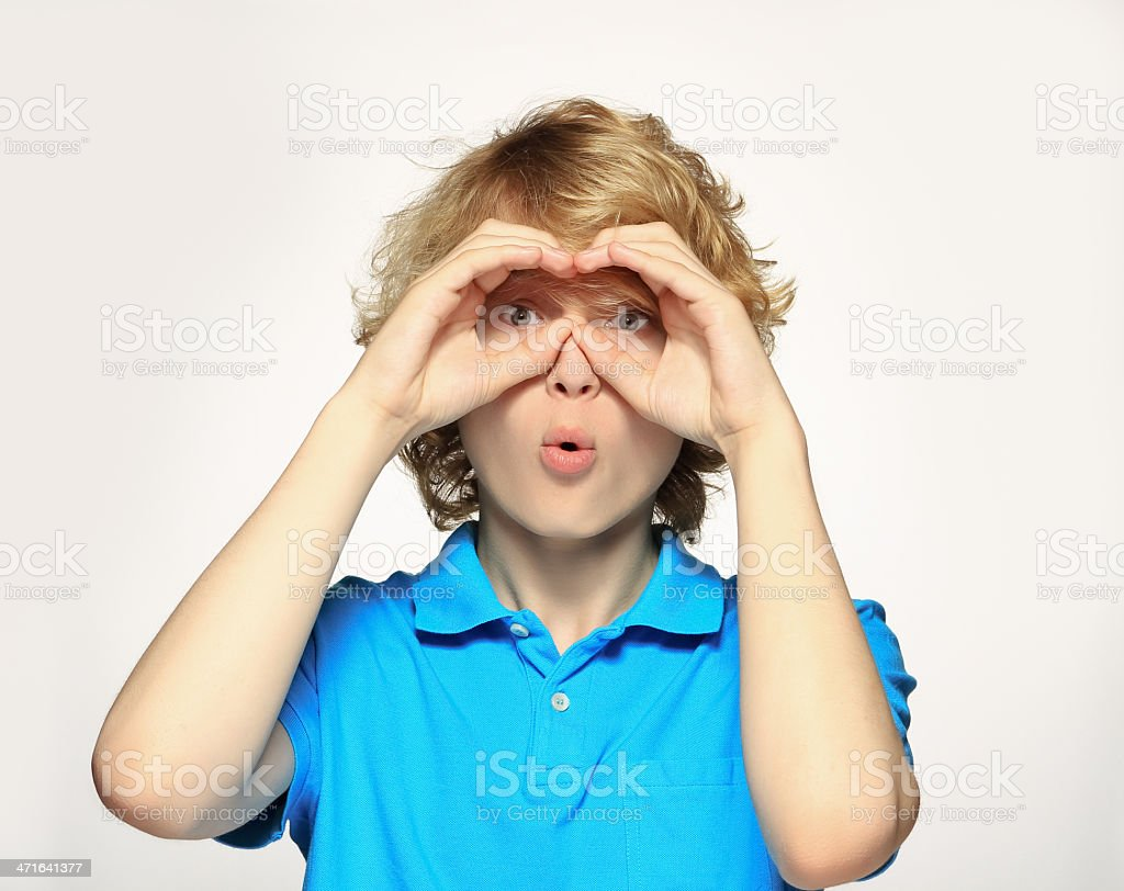 Teenage boy   shielding eyes and looking stock photo