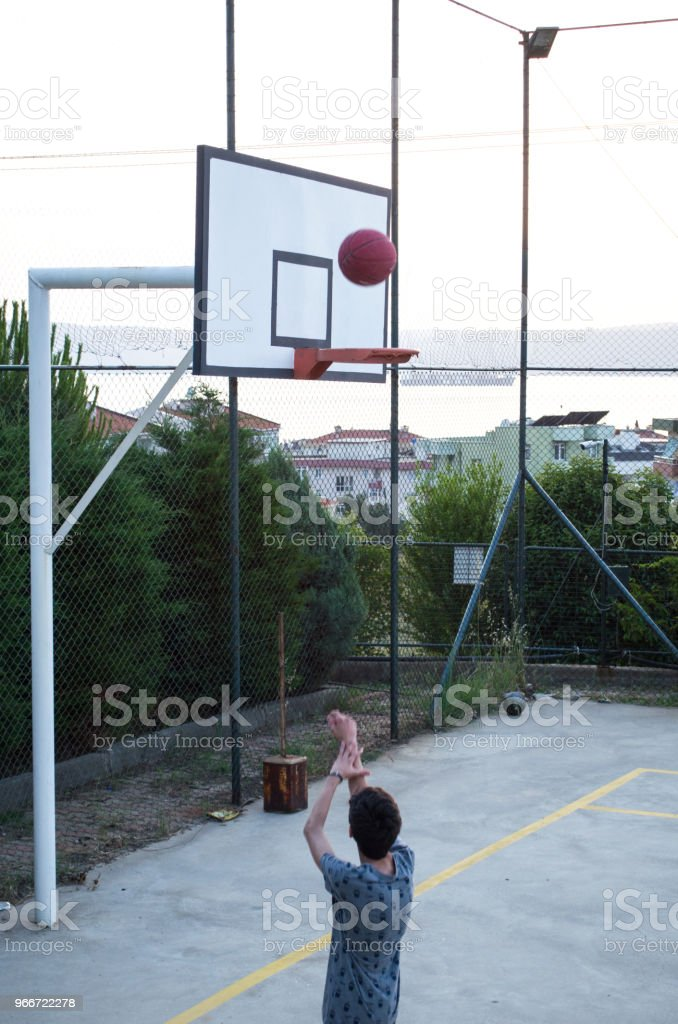 Teenage boy shooting at basket on outdoor basketball court