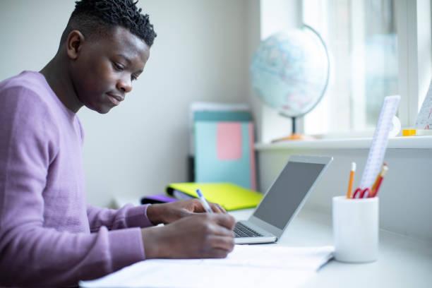 Teenage Boy sitzt am Schreibtisch, der Hausaufgaben auf dem Laptop – Foto