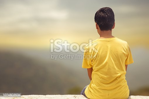 A young boy sitting on a rock on a cliff edge is looking the mountains all around him
