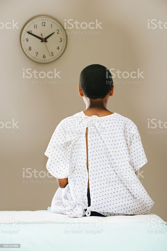 Teenage boy (12-13) sitting with surgical gown in patient room, stock photo