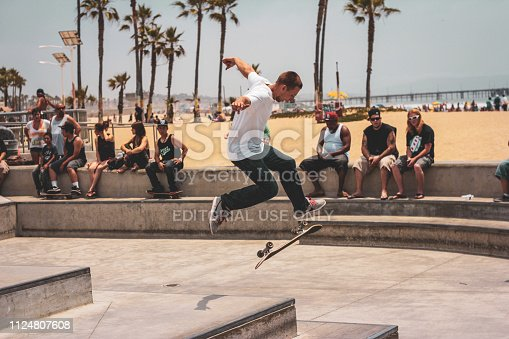Venice Beach, California - June 2013 - Teenage boy doing a kickflip infront of bystanders at the Venice Beach Skatepark.