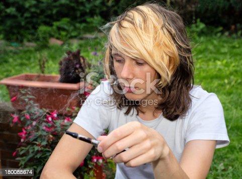 istock Teenage boy smoking an electronic cigarette 180088674