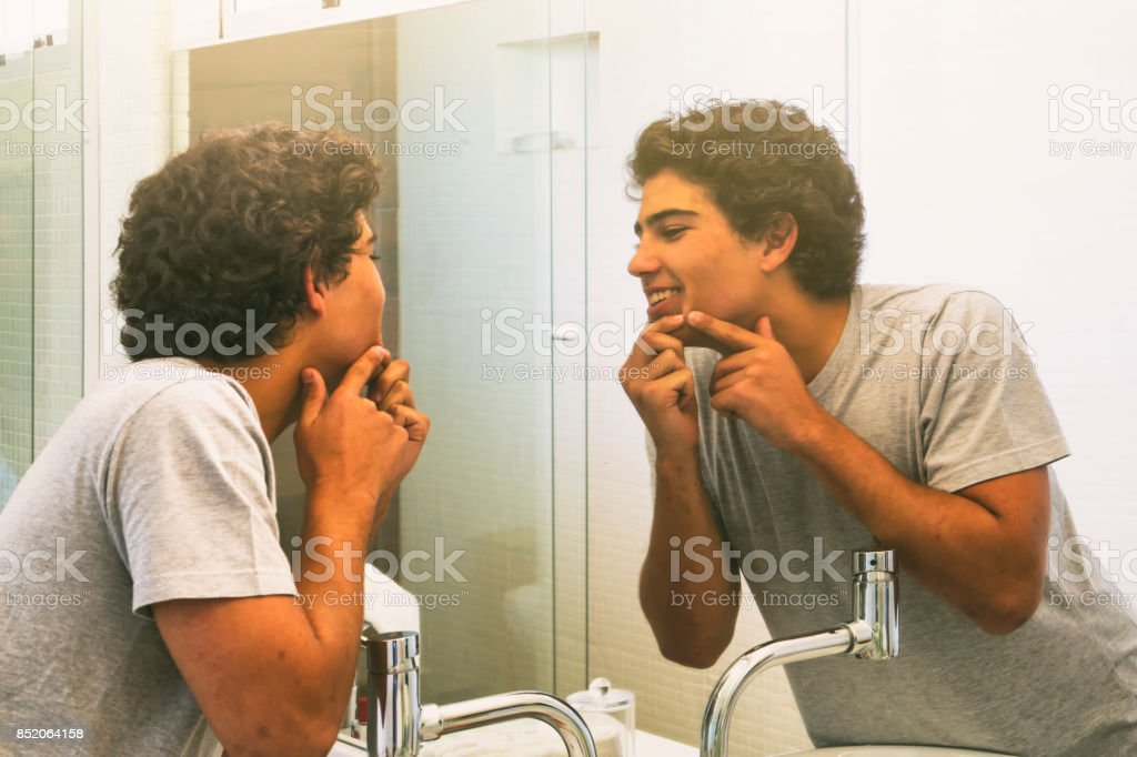 Teenage boy squeezing a pimple. stock photo