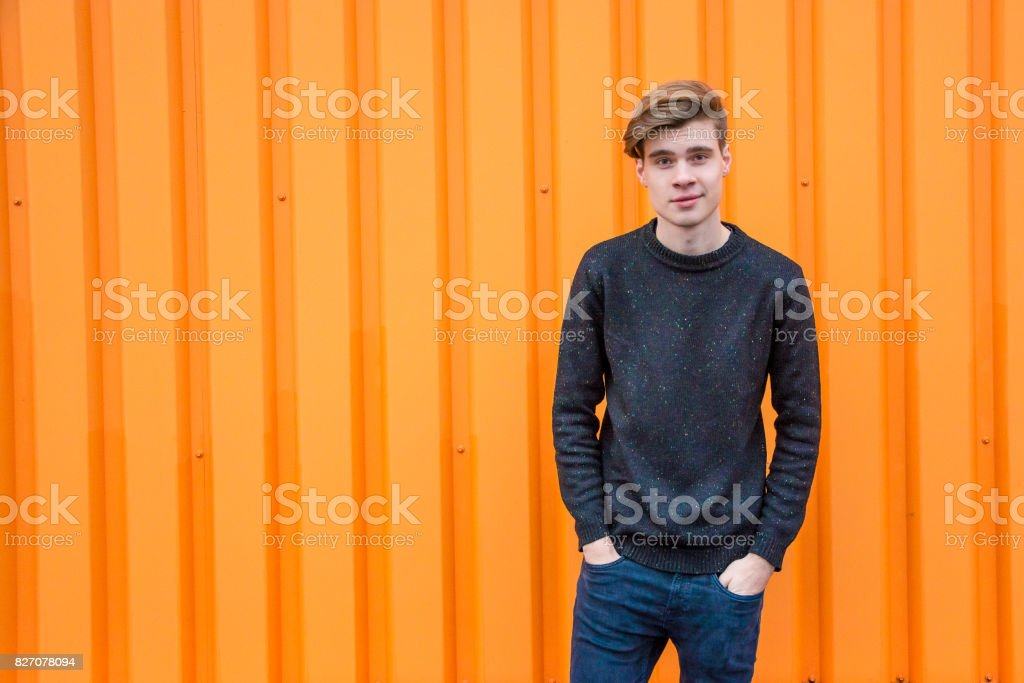 Teenage boy standing over contrasting orange background with copyspace stock photo