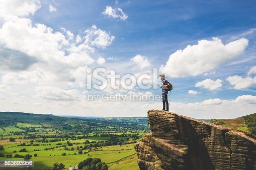 A teenage boy stands at the edge of a rocky outcropping while rambling along The Roaches in Peak District National Park, United Kingdom. He looks over the rolling green countryside of Staffordshire on a warm summer day.
