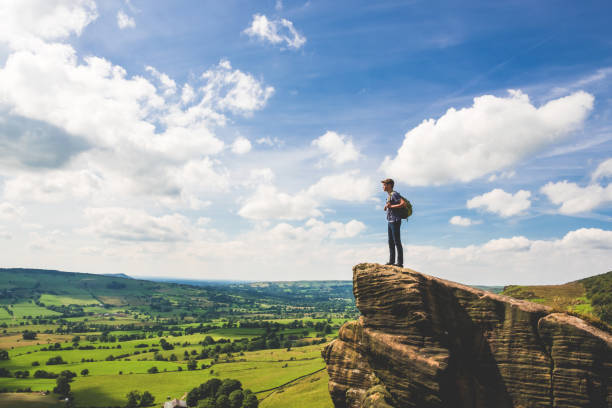 teenage boy stands at edge in peak district - outcrop stock pictures, royalty-free photos & images