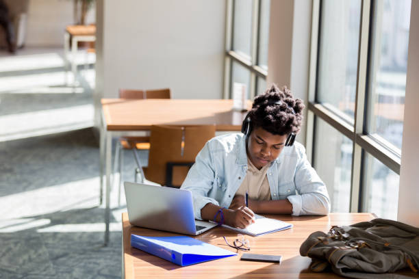 Teenage boy studies in school library African American teenage boy writes something in a notebook while studying in the campus library. An open laptop is on the table. He is wearing wireless headphones. university stock pictures, royalty-free photos & images