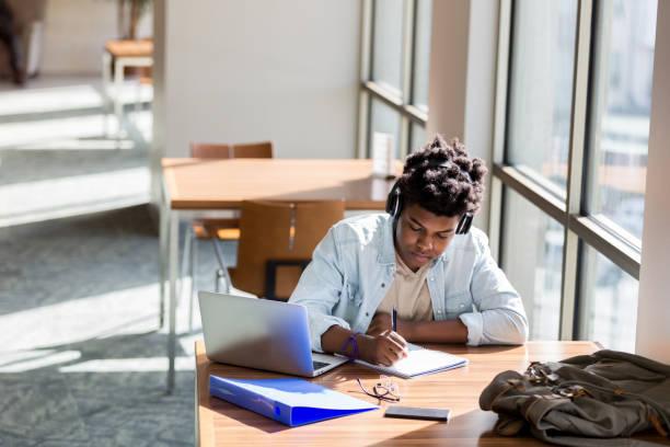 teenage boy studies in school library - university стоковые фото и изображения