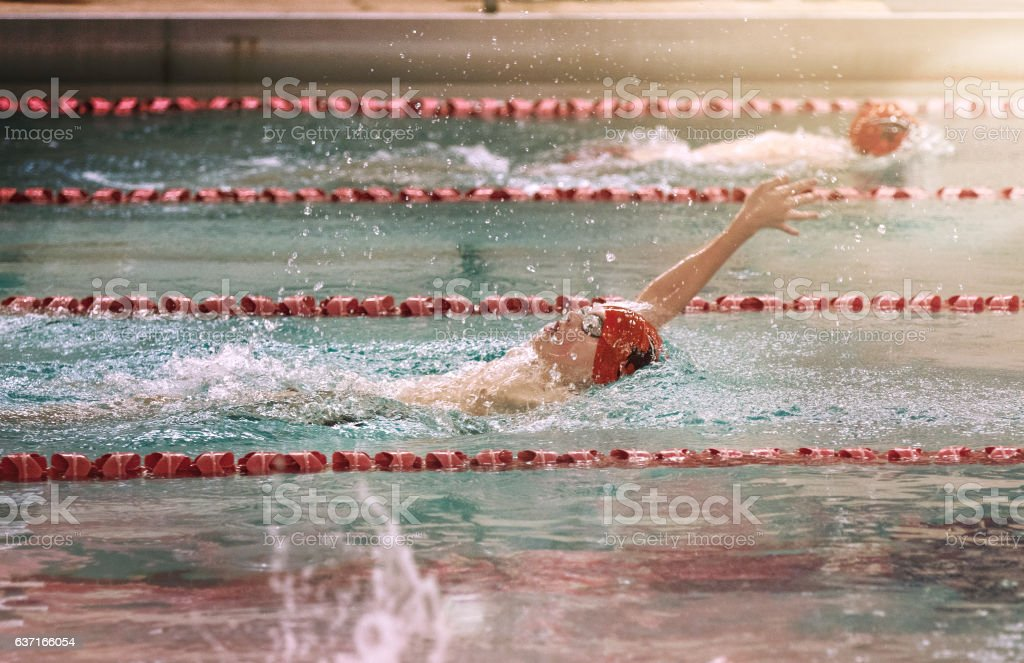 Teenage Boy Swimming Backstroke at a High School Swim Meet stock photo