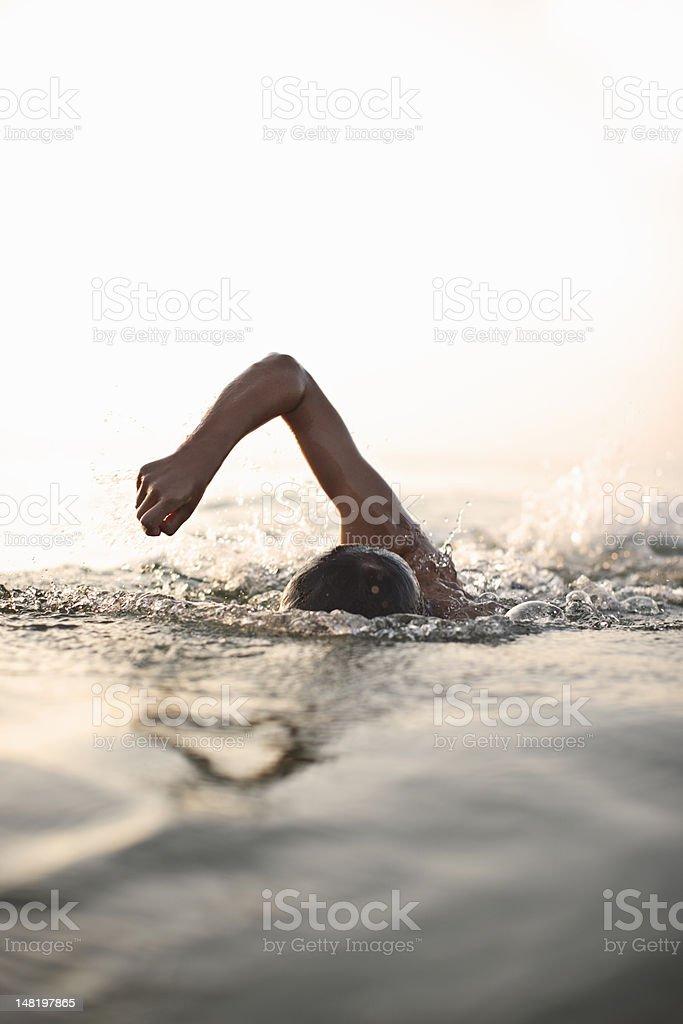Teenage boy swimming in water stock photo