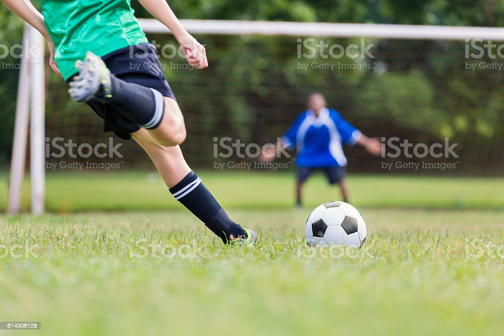 Teenage boy takes penalty shot during soccer game stock photo