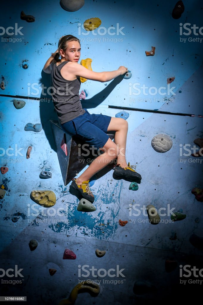 Teenage Boy Training Climbing On Indoor Climbing Wall stock photo