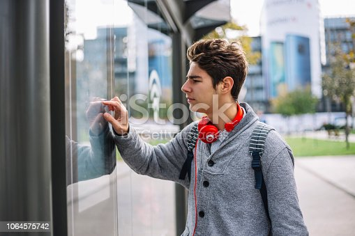 Student using a touch screen finding informations online in city streets