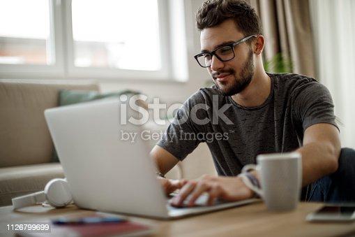istock Teenage boy using laptop at home 1126799699
