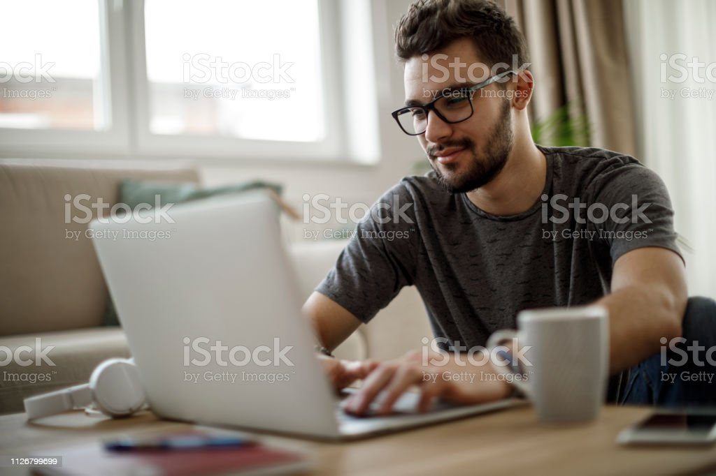 Teenage boy using laptop at home stock photo