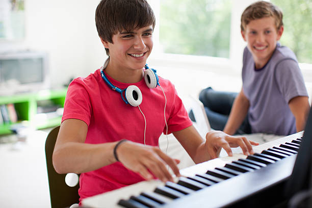 Teenage boy watching friend play electronic piano keyboard  keyboard player stock pictures, royalty-free photos & images