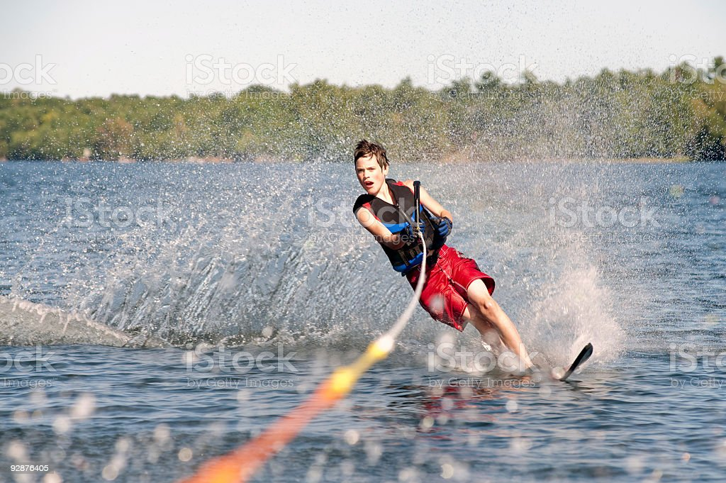 Teenage boy waterskiing on a lake stock photo