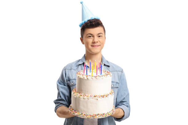 Teenage boy wearing a party hat and holding a cake stock photo