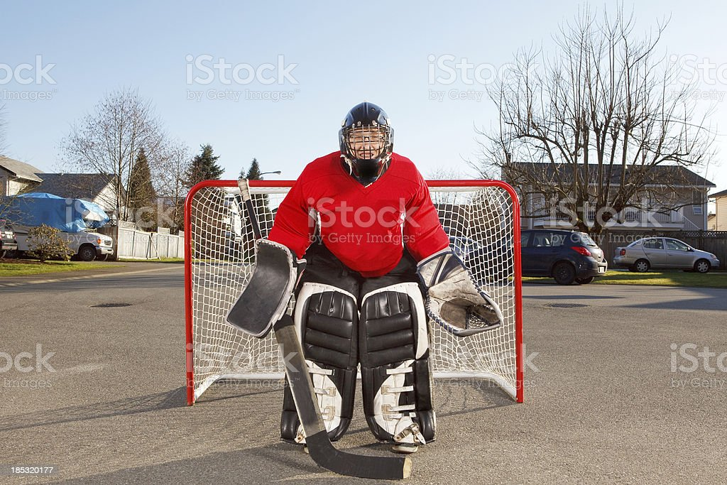 Teenage boy wearing goalie equipment for street hockey stock photo