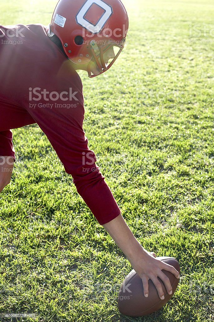 Teenage boy (14-15) wearing helmet playing American football royalty-free stock photo