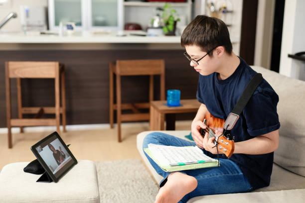 ダウン症の10代の少年は、インターネット上で自宅で遠くの学習音楽レッスンを受けています - disabilitycollection ストックフォトと画像
