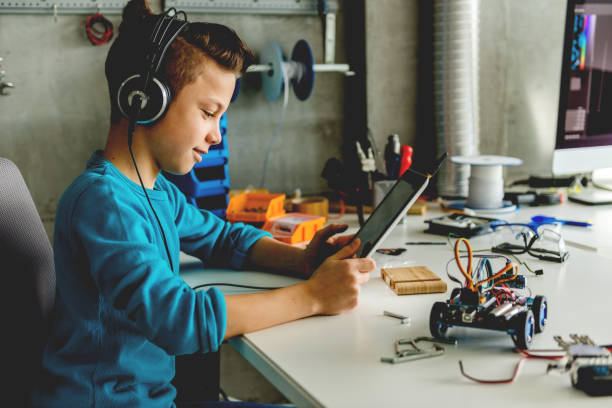 Teenage boy with headphones holding digital tablet stock photo