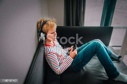 istock teenage boy with headset using mobile phone at home 1180197421