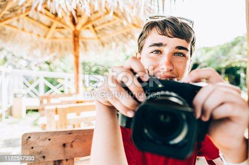 Teenage boy  at cabana at summer resort, using retro digital camera. He is enjoying summer vacation in Caribbean.