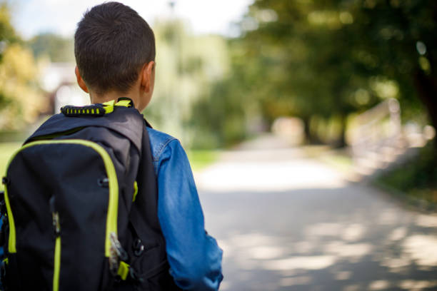 Teenage boy with school bag going home from school stock photo