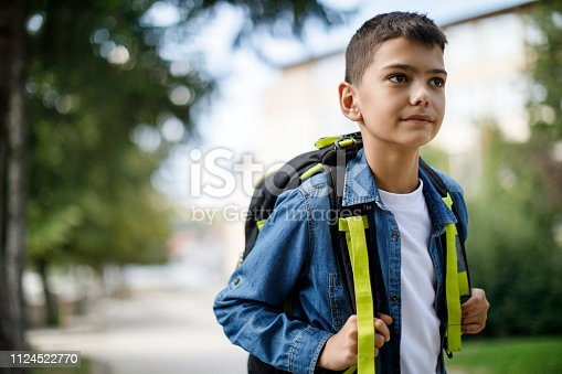 istock Teenage boy with school bag going home from school 1124522770