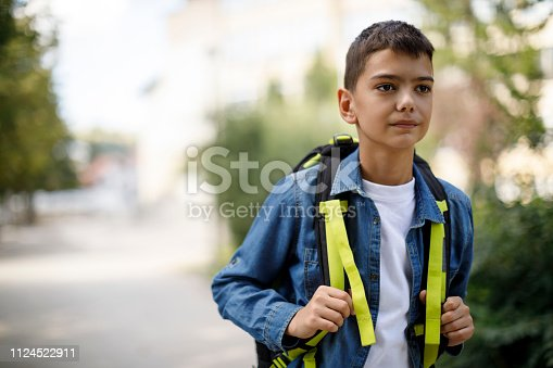 istock Teenage boy with school bag going home from school 1124522911
