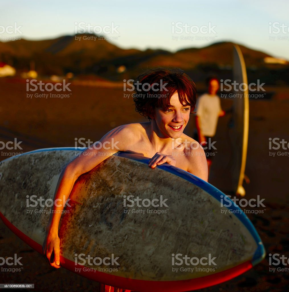 Teenage boy (14-15) with surfboard on beach royalty-free stock photo