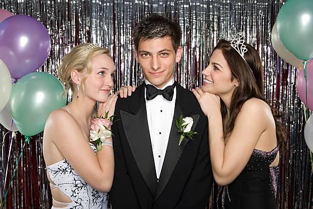 teenager junge mit zwei mädchen in der high school-abschlußball - high school abschlußball stock-fotos und bilder