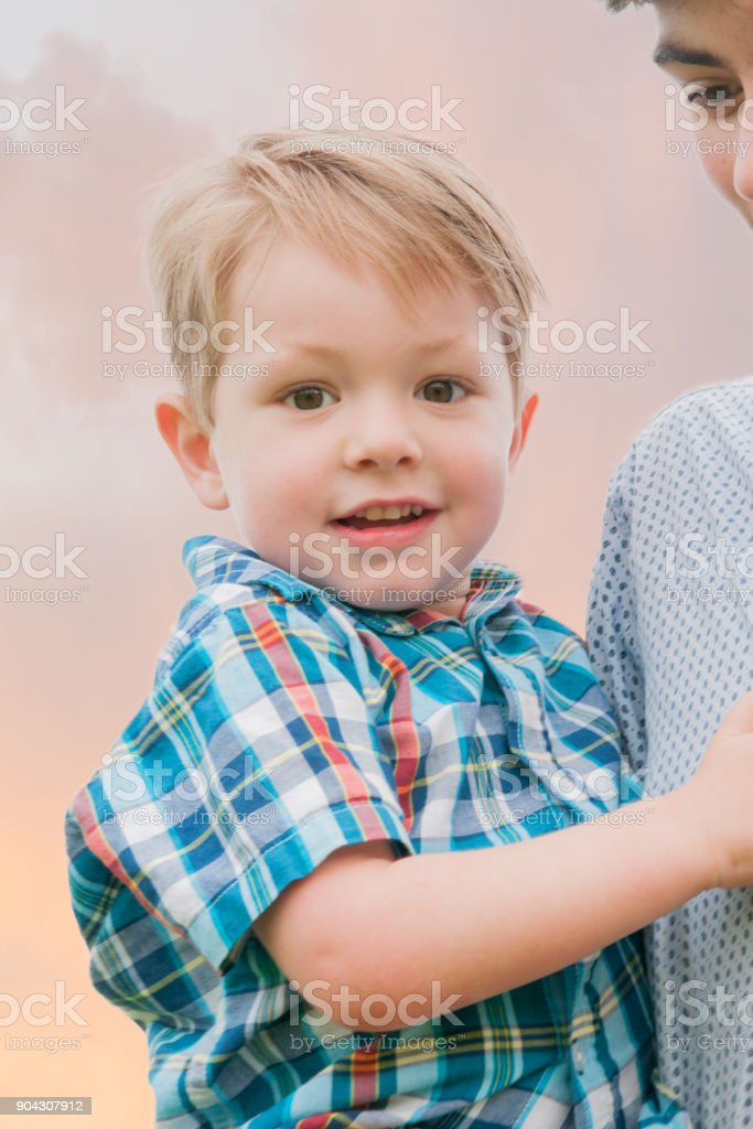 Teenage boy with younger brother in arms walking in a field stock photo