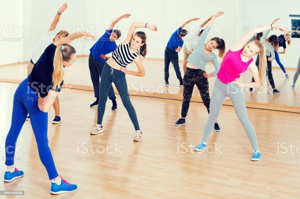 happy european teenage boys and girls with trainer stretching in...