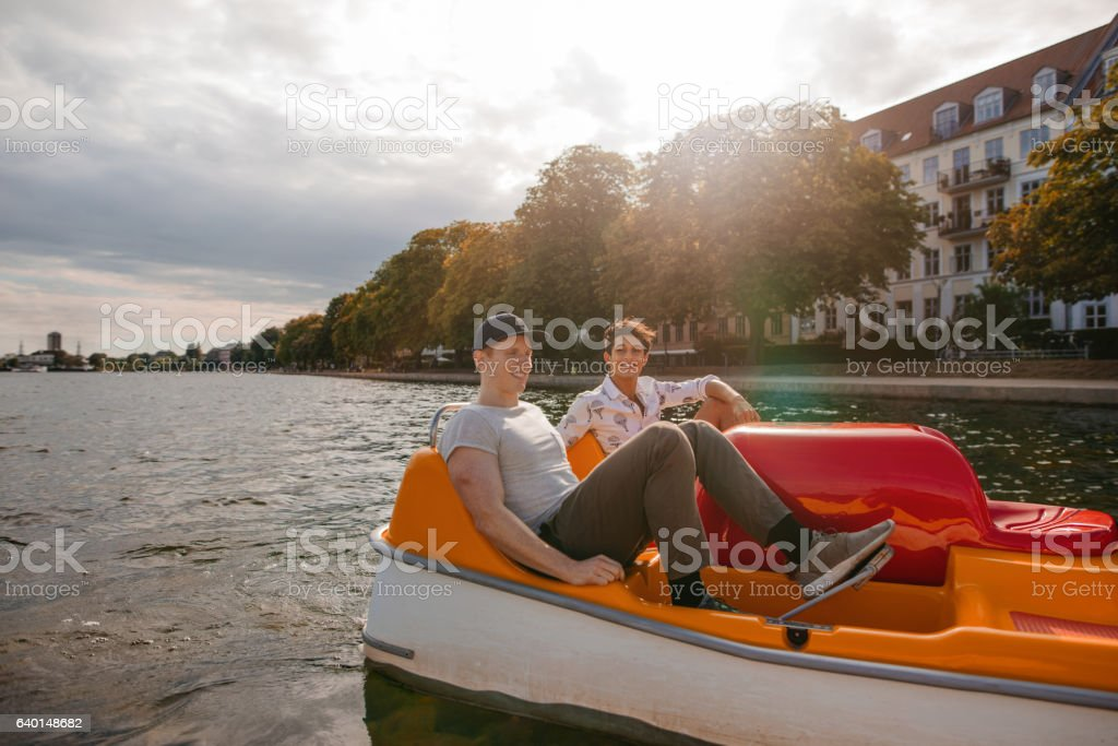 Teenage boys boating on the lake in city stock photo