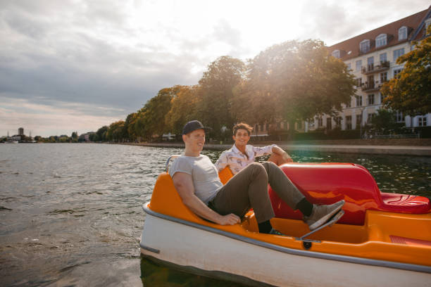 teenage boys boating on the lake in city - pédalo photos et images de collection
