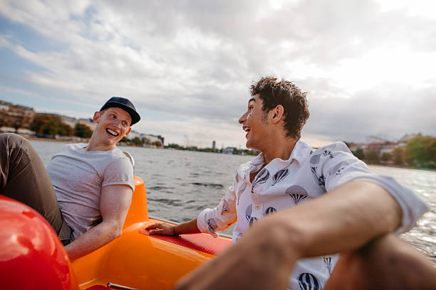 teenage boys enjoying boating in the lake - pédalo photos et images de collection
