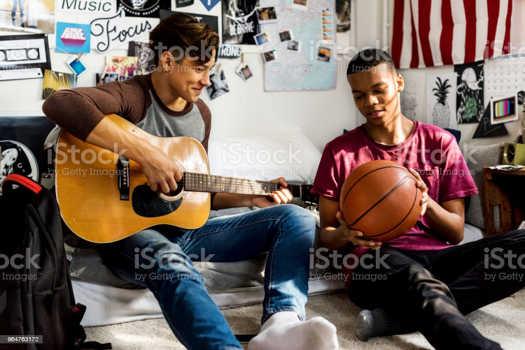 Teenage boys hanging out in a bedroom music and sports hobby concept royalty-free stock photo