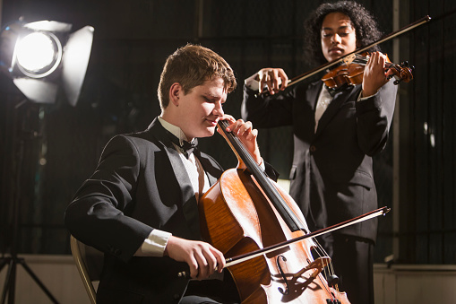 Teenage boys playing double bass and violin in concert
