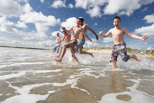 Teenage boys playing on beach stock photo