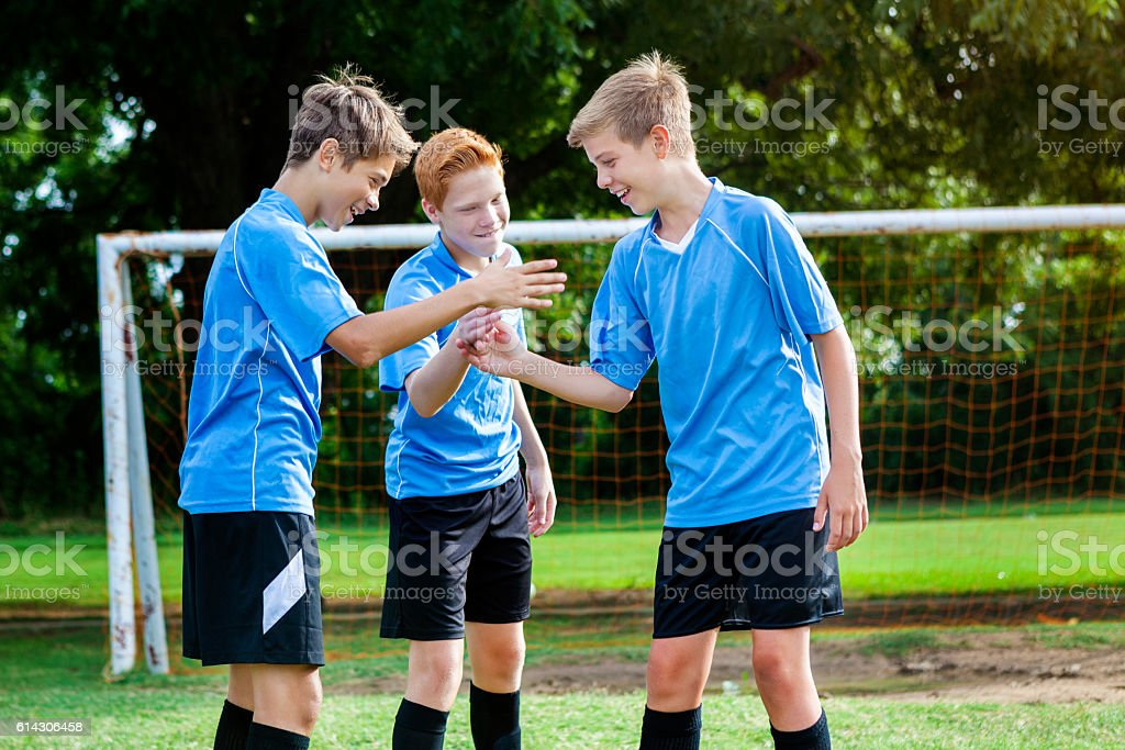 Teenage boys soccer team congratulate one another after winning game stock photo