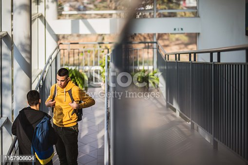 Teenage friends standing in a school hallway and communicating.