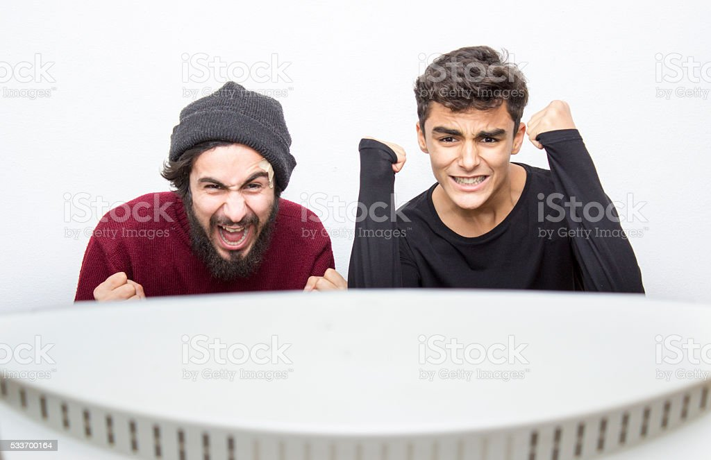 Teenage boys watching tv in excitement over colored background....